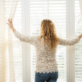 A woman opening her sheer window treatments to allow light into her home.